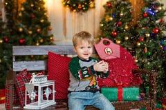 小白肤金发的迷人的男孩坐长凳和举行雪在Th 图库摄影