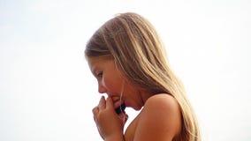 小白肤金发的长发女孩咬住三明治 免版税库存图片