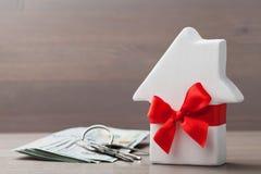 小白色房子装饰了与钥匙串的红色弓丝带和现金金钱在木桌上 礼物、房地产或者买的新的家 免版税库存照片