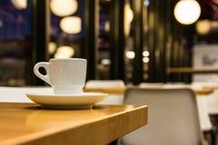小白色浓咖啡茶杯在表上在别致的减速火箭的咖啡馆 库存照片