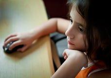小的与计算机的女孩拉丁工作在家 免版税库存图片