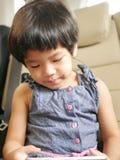小的亚洲女婴藏品和使用一个手机,当坐在一辆驾驶的汽车时 免版税图库摄影