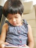 小的亚洲女婴藏品和使用一个手机,当坐在一辆驾驶的汽车时 图库摄影