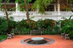 小的喷泉在有长凳的一个庭院里 免版税库存照片