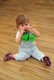 小的女孩坐与玩具的木楼层和作用 免版税图库摄影
