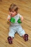 小的女孩坐与玩具的木楼层和作用 库存图片