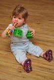 小的女孩坐与玩具的木楼层和作用 库存照片