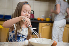 去小的女孩搅拌薄煎饼的面团 免版税库存图片