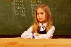 小的女孩 有严肃的面孔的小女孩在学校 学校教训的小女孩 小女孩准备学习 愉快 库存图片