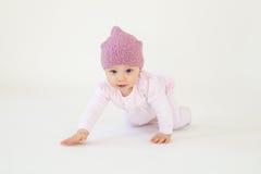 小的女婴佩带的帽子坐被隔绝的地板 库存图片