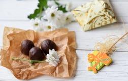 小的当前,鲜花和一些巧克力糖白色木表面上 库存图片