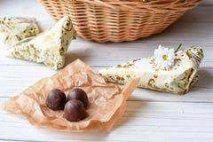小的当前,鲜花和一些巧克力糖白色木表面上 库存照片