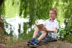小的愉快的男孩阅读书 免版税库存图片