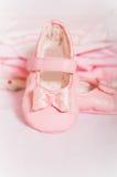 小的桃红色童鞋和婴孩衣裳 库存图片