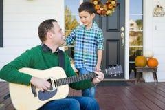小的混合的族种中国和白种人儿子唱歌歌曲和Pla 免版税库存照片