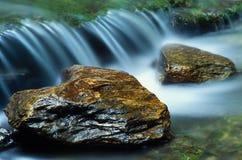 小的瀑布和一个对河岩石 免版税库存照片