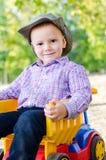 小的男孩坐玩具卡车 库存图片