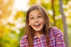 小的笑的女孩画象在秋天公园 免版税库存图片