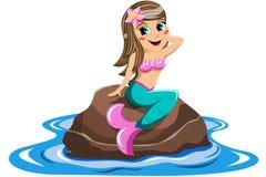 小的美人鱼坐的岩石海 库存照片