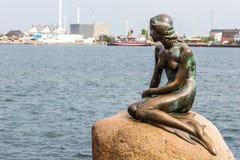 小的美人鱼是一个古铜色雕象由Edvard Eriksen,描述美人鱼 雕塑在岩石被显示由watersid 免版税图库摄影