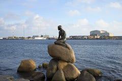 小的美人鱼的雕塑在哥本哈根港口码头的背景的  丹麦 免版税库存照片