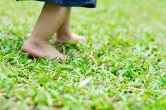 小的脚走在绿草的婴孩 免版税库存图片