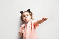 小的逗人喜爱的女孩举行刷子为在手上组成在灰色背景 库存图片