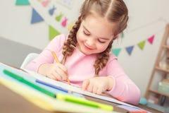 小的逗人喜爱的女孩在家教育概念坐的图画贺卡为妇女快乐` s的天 库存照片