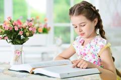小的逗人喜爱的女孩阅读书 免版税图库摄影