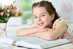 小的逗人喜爱的女孩阅读书 图库摄影