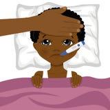 小的非裔美国人的男孩不适在与温度计的床上在他的嘴和母亲s在他的前额朝向 免版税库存图片