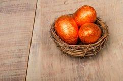 小的鸟的嵌套用橙色箔鸡蛋 库存图片