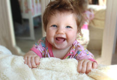 小的婴儿笑,站立在床附近 库存照片