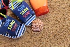 小的婴孩凉鞋和化妆水在海滩 免版税库存图片