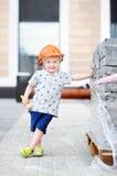 小的建造者画象在安全帽的有运转的锤子的户外 图库摄影