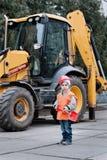 小的建造者画象在运转户外在拖拉机挖掘机附近的安全帽的 库存照片