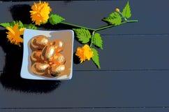 小盘用金黄巧克力复活节彩蛋和黑暗的木背景 免版税库存照片