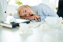 小睡在书桌上的被用尽的女实业家在工作 免版税库存图片