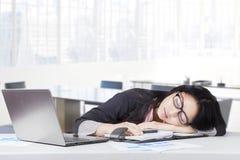 小睡在办公室的被用尽的女性企业家 免版税库存照片