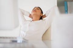 小睡在她的书桌的偶然女实业家 免版税库存图片