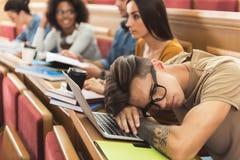 小睡在教训的疲乏的人在大学 免版税库存照片