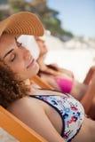 小睡在轻便折叠躺椅的海滩的美丽的妇女 免版税图库摄影