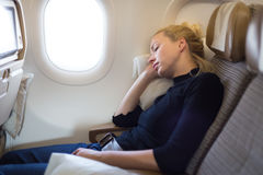 小睡在飞机的疲乏的白肤金发的偶然白种人妇女 库存图片