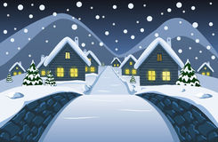 从小石桥梁的看法在夜多雪的村庄 免版税库存照片
