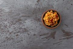 小碗的顶视图在灰色背景抵消的墨西哥米和豆 免版税库存照片
