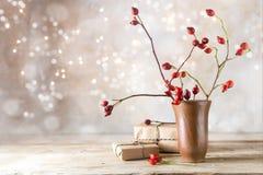 小礼物小包和野玫瑰果分支在一张土气木桌上 免版税库存图片