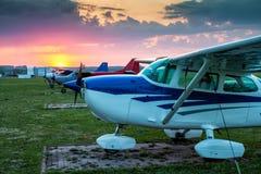 小私有飞机停放在机场在美丽如画的日落 免版税图库摄影