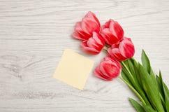 小空白的纸片和桃红色郁金香在轻的木背景 顶视图,文本的空间 免版税库存照片