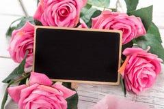 小空白的黑板为华伦泰` s或母亲妇女天 背景桃红色玫瑰 库存图片