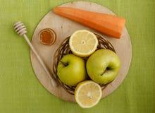 小篮子用果子 苹果,柠檬,在桌上的红萝卜 免版税图库摄影